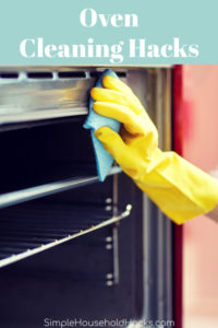 woman cleaning an oven with a sponge