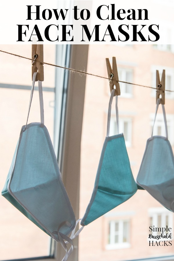 cloth face masks hanging by clothes pins from a laundry line to dry
